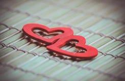 Dos corazones rojos en la servilleta de bambú Foto de archivo libre de regalías