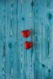 Dos corazones rojos en un fondo azul con la textura de madera fotografía de archivo
