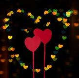Dos corazones rojos en un fondo del bokeh de los corazones Fotografía de archivo