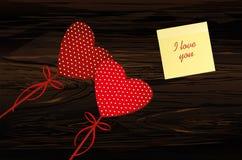 Dos corazones rojos en un palillo con el arco y la hoja de papel amarilla para Fotografía de archivo