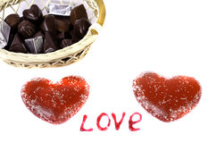 Dos corazones rojos en una cesta blanca del fondo con el chocolate y t Imagen de archivo