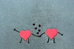 Dos corazones rojos que llevan a cabo las manos en un fondo gris Corazones con las manos y los pies pintados Corazones cariñosos Fotos de archivo libres de regalías