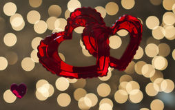 Dos corazones rojos se entrelazan y se fijan contra un fondo de las luces del centelleo Imagen de archivo