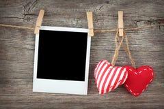 Dos corazones rojos y foto inmediata en blanco Imagen de archivo libre de regalías