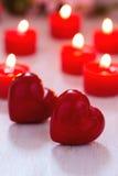 Dos corazones rojos y velas ardientes en la tabla Imágenes de archivo libres de regalías