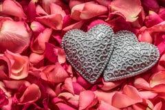 Dos corazones tallados decorativos en el fondo rojo de pétalos color de rosa imágenes de archivo libres de regalías