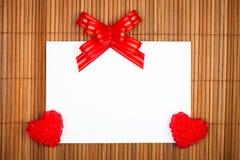 Dos corazones y arqueamientos rojos con la tarjeta de papel Fotos de archivo libres de regalías