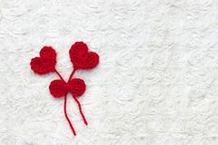Dos corazones y cintas rojos de las lanas del ganchillo en el fondo blanco del ganchillo El concepto para el 14 de febrero, día d imágenes de archivo libres de regalías