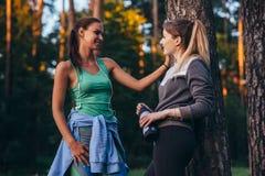 Dos corredores femeninos que se relajan después del entrenamiento que se coloca cerca del árbol que habla en parque Fotos de archivo libres de regalías