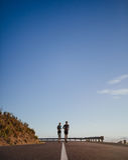 Dos corredores jovenes que corren en la carretera nacional abierta Imágenes de archivo libres de regalías