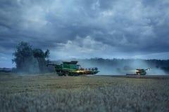 Dos cosechadoras en un campo por la tarde Imagen de archivo libre de regalías