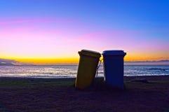 Dos cubos de la basura en la playa en la puesta del sol Fotos de archivo libres de regalías