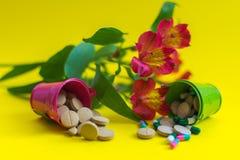 Dos cubos por completo de píldoras con las flores fotografía de archivo