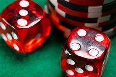 Dos cubos rojos de los dados, mentira en una tabla verde Imagen de archivo libre de regalías