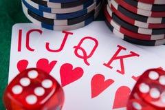 Dos cubos rojos en un sistema de tarjetas con un traje, en la mesa de juegos Imagen de archivo libre de regalías