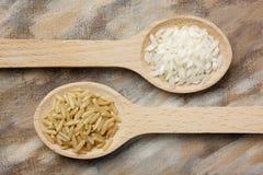 Dos cucharas de madera con los granos del arroz blanco y moreno Foto de archivo libre de regalías