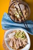 Dos cuencos de ramen de los tallarines de la sopa, de apio, de pollo y de servilleta azul Fotos de archivo libres de regalías