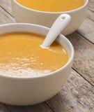 Dos cuencos de sopa de la calabaza en la tabla de madera imagen de archivo