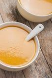 Dos cuencos de sopa de la calabaza en la tabla de madera fotos de archivo