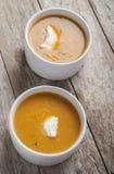 Dos cuencos de sopa de la calabaza en la tabla de madera fotografía de archivo