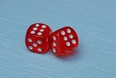 Dos dados rojos están en una tabla azul Foto de archivo libre de regalías