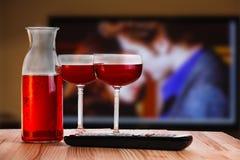 Dos de cristal y garrafa del vino con el telecontrol de la TV Foto de archivo