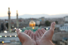 Dos de manos abiertas a rogar delante de la tumba de Zeinab Imagenes de archivo
