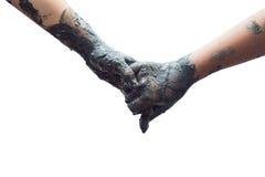 Dos de manos de los niños se están sosteniendo con la arcilla del fango Aislado en whi Fotografía de archivo