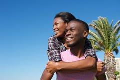 Dos de transport de sourire d'amie de jeune homme dessus Photographie stock libre de droits