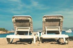 Dos deckchairs vacíos en una playa arenosa que hace frente al océano, a los cielos azules y a un pequeño barco de la velocidad Imágenes de archivo libres de regalías