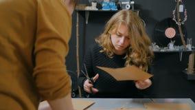 Dos decoradores de las mujeres profesionales, diseñadores que trabajan con el papel de Kraft metrajes