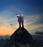 Dos del hombre de negocios asiático que se coloca encima del acantilado y de la mirada de la roca Imagen de archivo