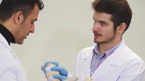 Dos dentistas de sexo masculino que discuten el mandíbula moldean en la clínica dental imagen de archivo libre de regalías