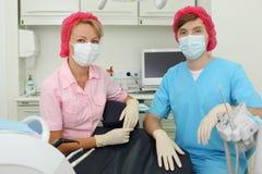 Dos dentistas en máscaras se sientan en clínica dental Imagen de archivo