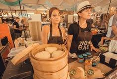 Dos dependientas hermosas que venden la comida asiática del dim sum en el festival al aire libre popular de la comida de la calle Fotos de archivo