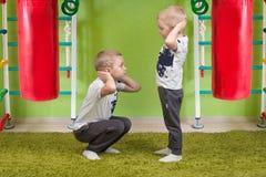 Dos deportes del juego de los hermanos Posición en cuclillas junto Deporte y salud imagen de archivo libre de regalías