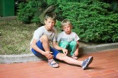 Dos desamparados sin hogar sin cruzar de los hermanos del muchacho se sientan en el encintado a finales de la tarde Imagen de archivo libre de regalías