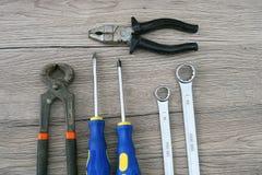 Dos destornilladores, dos llaves, dos alicates colocados en el de madera imagenes de archivo