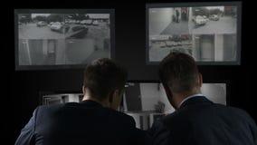 Dos detectives que comprueban expedientes de la cámara de vigilancia después del crimen, investigación metrajes