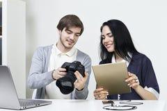 Dos diseñadores casuales sonrientes que ven las fotos en la cámara y el ordenador portátil, tableta en la oficina Imagen de archivo libre de regalías