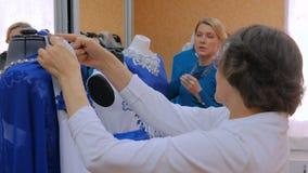 Dos diseñadores de moda que trabajan con la adaptación del modelo nuevo se visten en maniquí almacen de metraje de vídeo