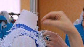 Dos diseñadores de moda que trabajan con la adaptación del modelo nuevo se visten en maniquí metrajes
