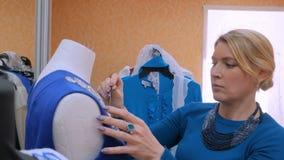 Dos diseñadores de moda que trabajan con la adaptación del modelo nuevo se visten en maniquí almacen de video