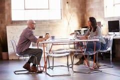 Dos diseñadores que se sientan en la mesa de reuniones que trabaja en el ordenador portátil Fotos de archivo