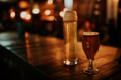Dos diversas cervezas en una tabla de madera, con las luces del pub en el fondo en la noche foto de archivo