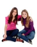 Dos diversas hermanas que se sientan en el piso Imágenes de archivo libres de regalías