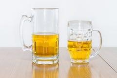 Dos diversas tazas de cerveza semillenas con la cerveza dorada fotografía de archivo