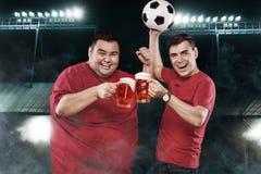 Dos diversiones del fútbol - felices y fútbol de observación del hombre gordo en el estadio de los deportes, tomando la cerveza y Imágenes de archivo libres de regalías