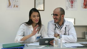Dos doctores alegres que tienen llamada video positiva vía la tableta metrajes