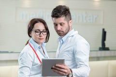 Dos doctores alegres que usan una tableta digital imágenes de archivo libres de regalías